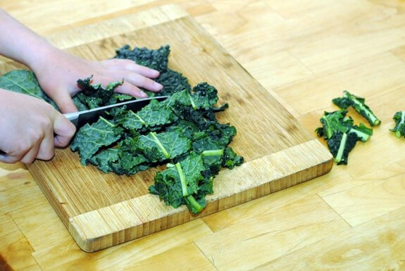 child chopping kale